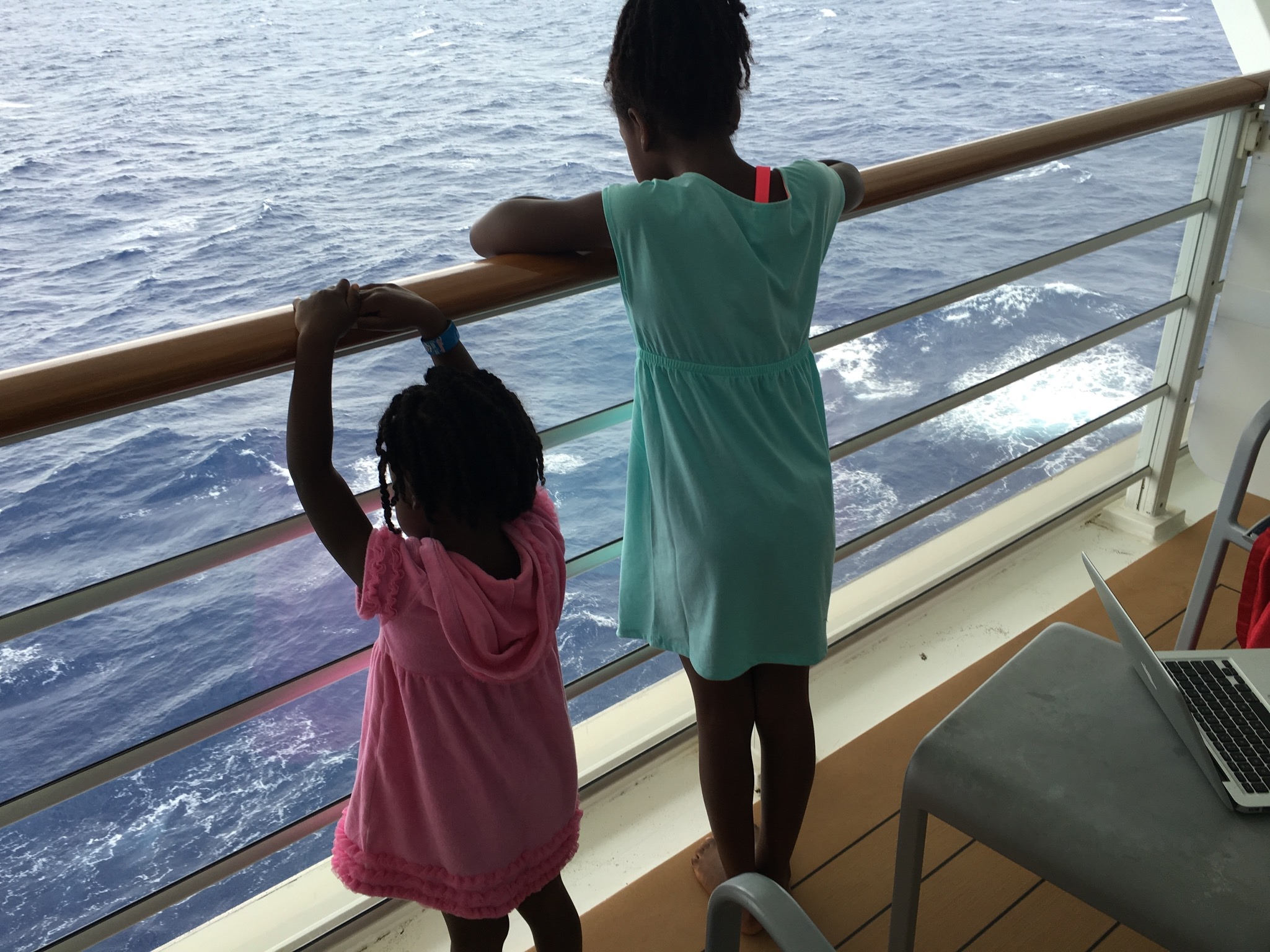 The girls, looking out over our stateroom's balcony at the overcast skies